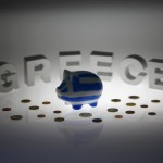 Piggybank painted in colours of Greek flag stands in front of letters spelling word 'GREECE' in this picture illustration taken in Berlin